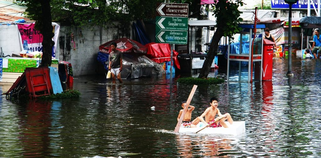 Boys in boat during flood in Bangkok
